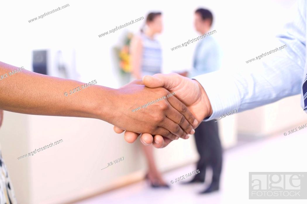 Stock Photo: Businessman and woman shaking hands, colleagues in background, close-up of hands.