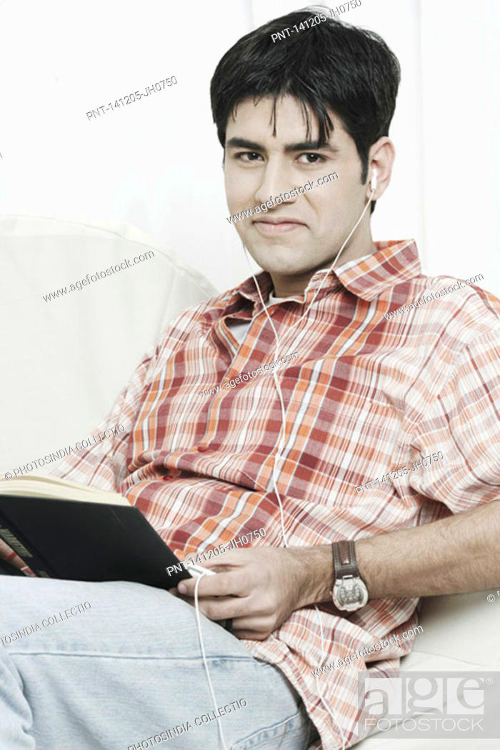 Stock Photo: Portrait of a young man with a book on his lap listening to an MP3 player.