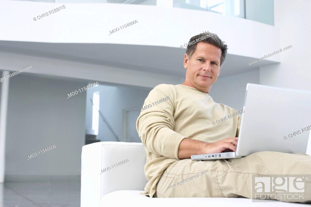 Stock Photo: Man using laptop on sofa in living room portrait.