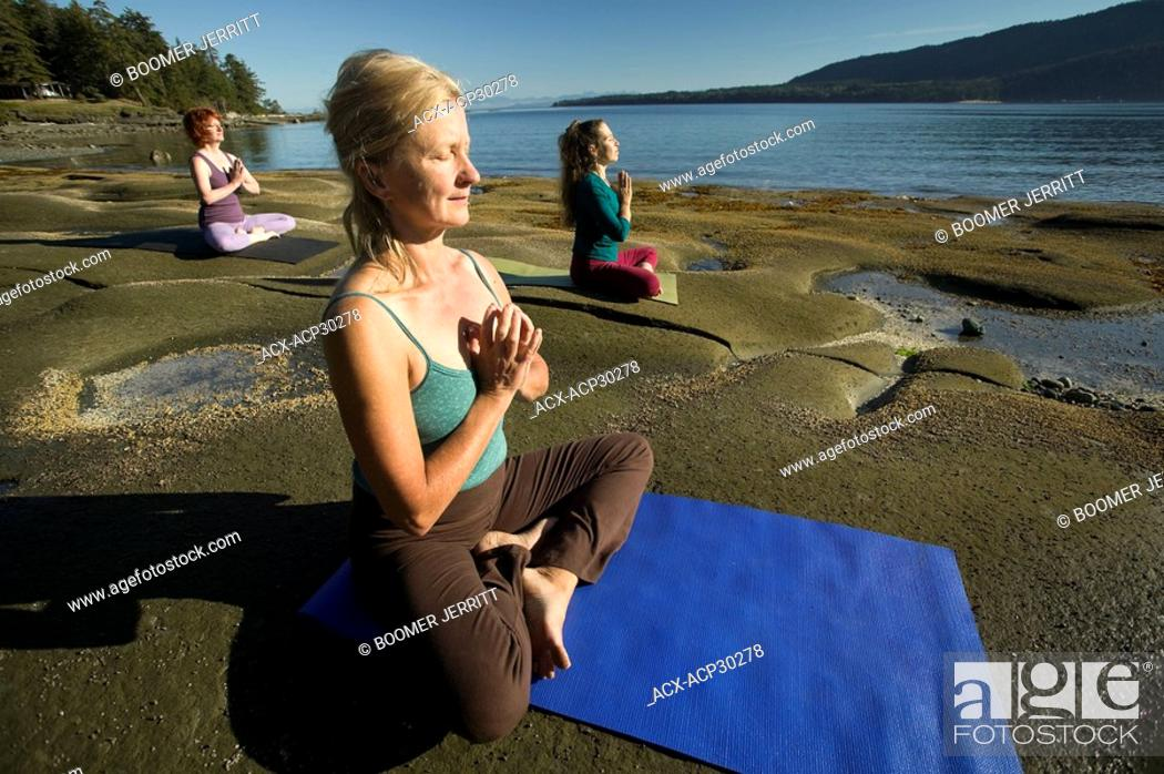 Stock Photo: Yoga practioners meditate and relax in the lotus position. Denman Island, The Comox Valley, Vancouver Island, British Columbia, Canada.