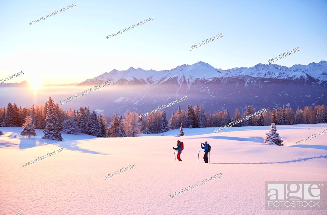 Stock Photo: Austria, Tyrol, couple snowshoeing at sunrise.