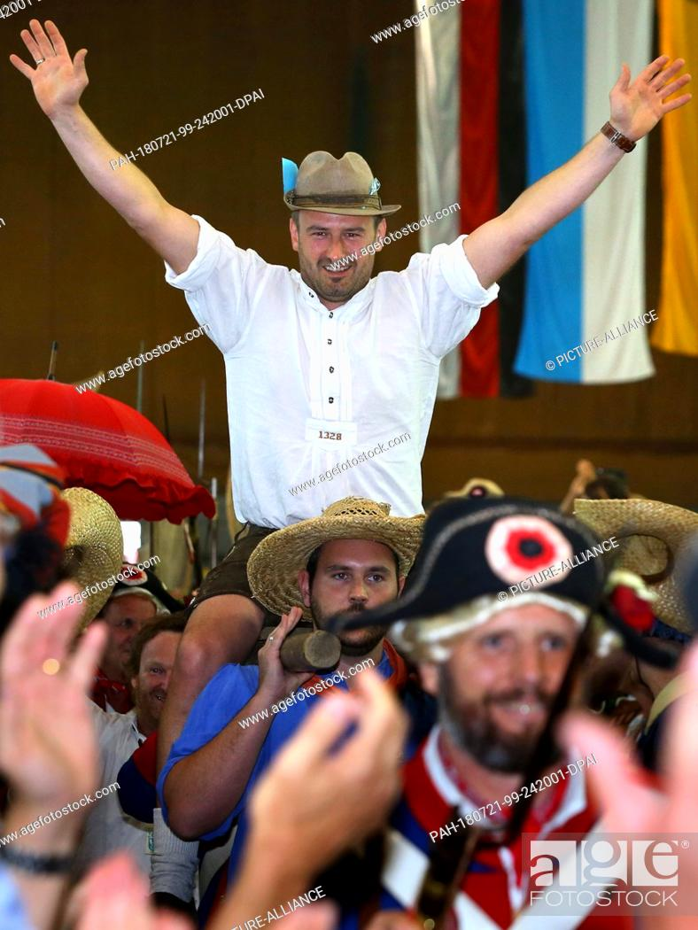 Stock Photo: 21 July 2018, Germany, Memmingen: Juergen Ziegler being carried into the Stadium Hall. Ziegler is the 2018 'Fisher King'.