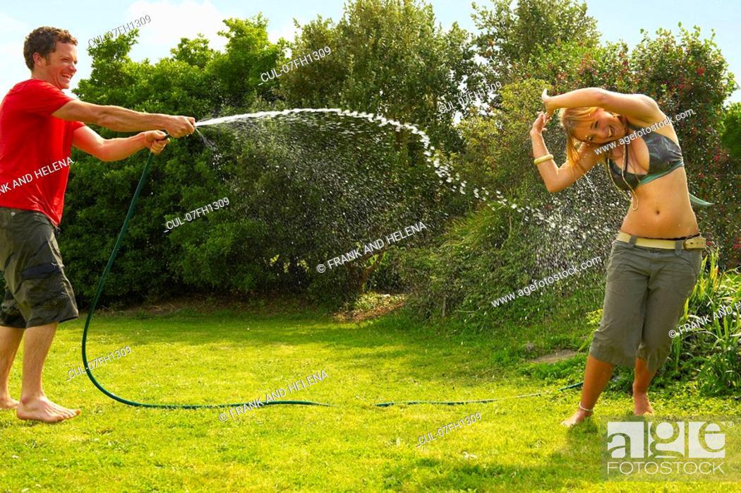 Stock Photo: Man spraying woman with garden hose.
