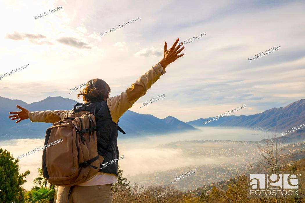 Imagen: Woman with outstretched arms and backpack enjoy panoramic view with sea of fog over alpine lake Maggiore with mountain in Ticino, Switzerland.