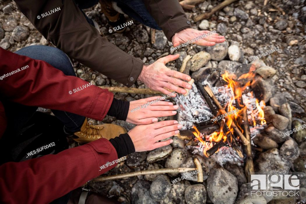 Photo de stock: Close-up of couple warming hands at camp fire.