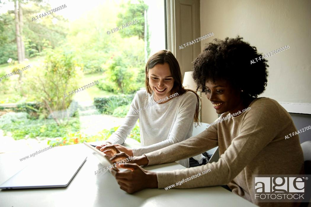Photo de stock: Smiling young women using digital tablet at home.