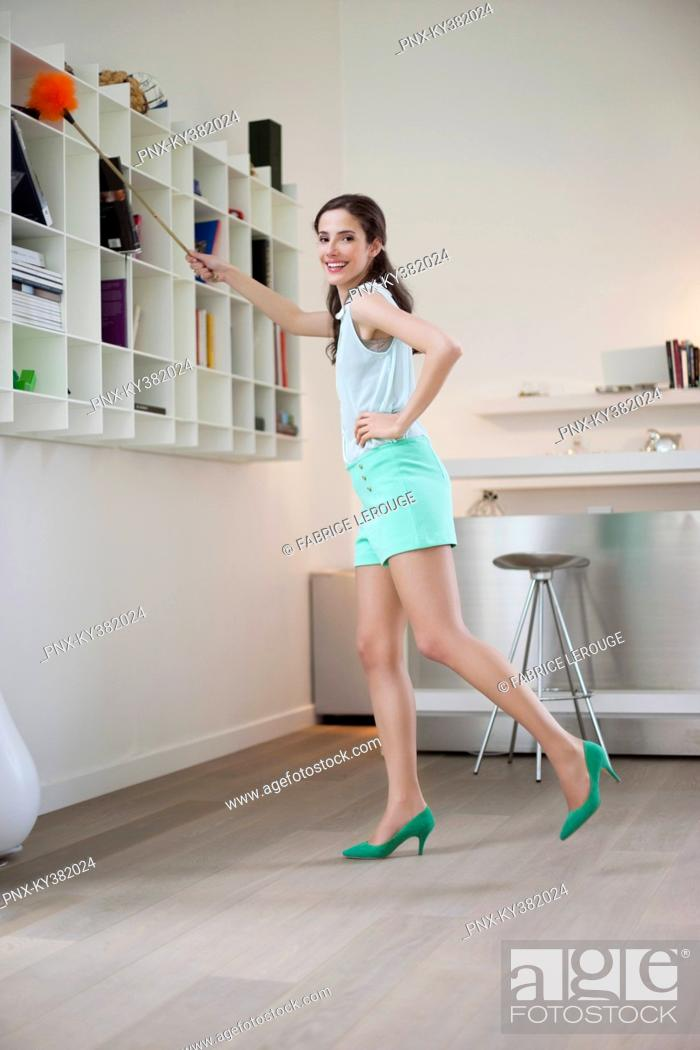 Stock Photo: Woman cleaning a bookshelf.