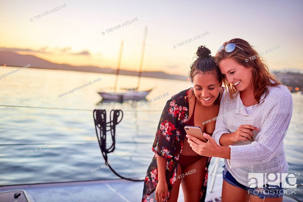 Stock Photo: Young women friends using smart phone on boat.