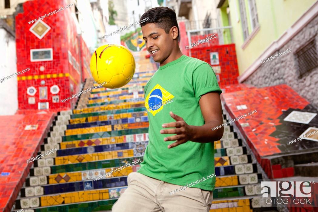 Photo de stock: Young man wearing Brazil top doing keepy uppys in front of the Escadaria Selaron steps in Rio de Janiero, Brazil.