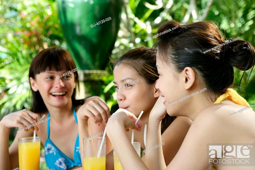 Photo de stock: Three teenage girls with juice glasses, holding straws.