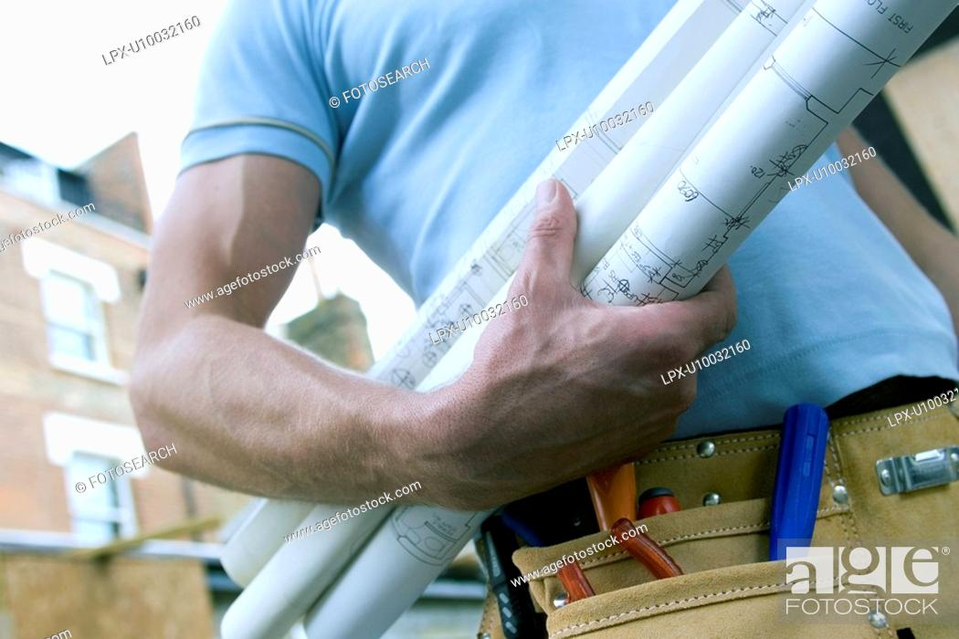 Stock Photo: Detail of a builder's hand with plans.