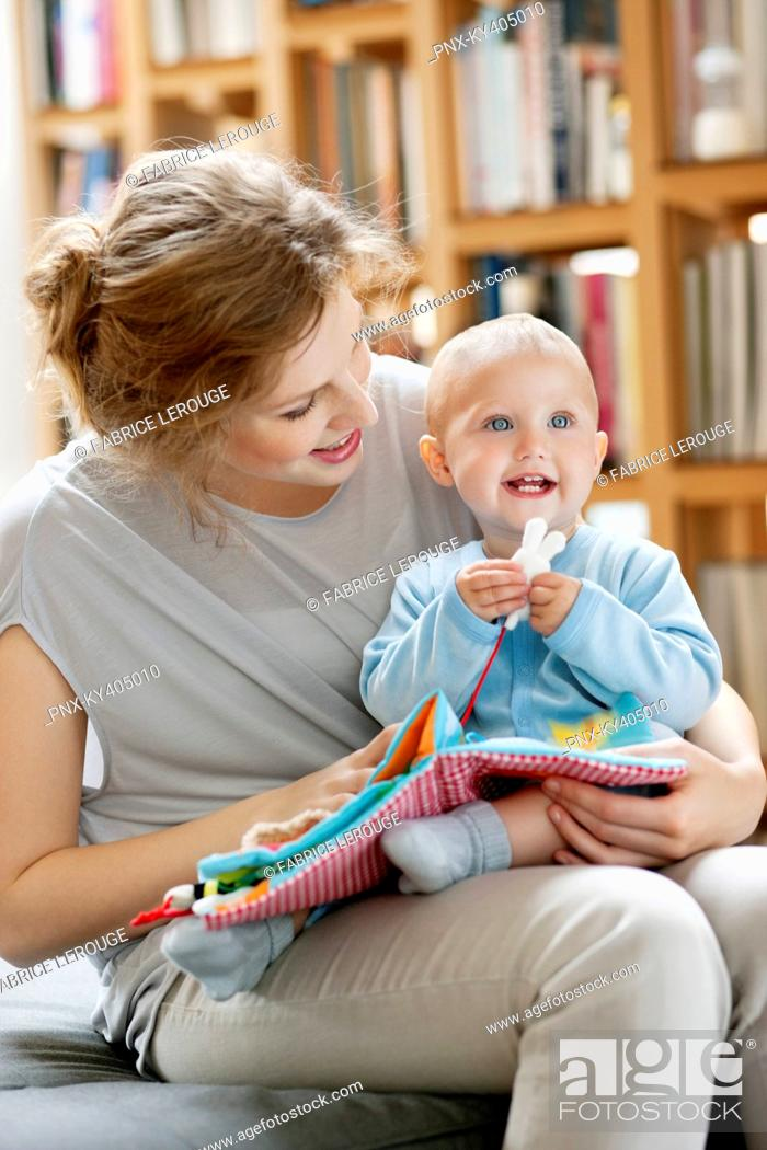 Stock Photo: Woman reading a story to her baby from a picture book.