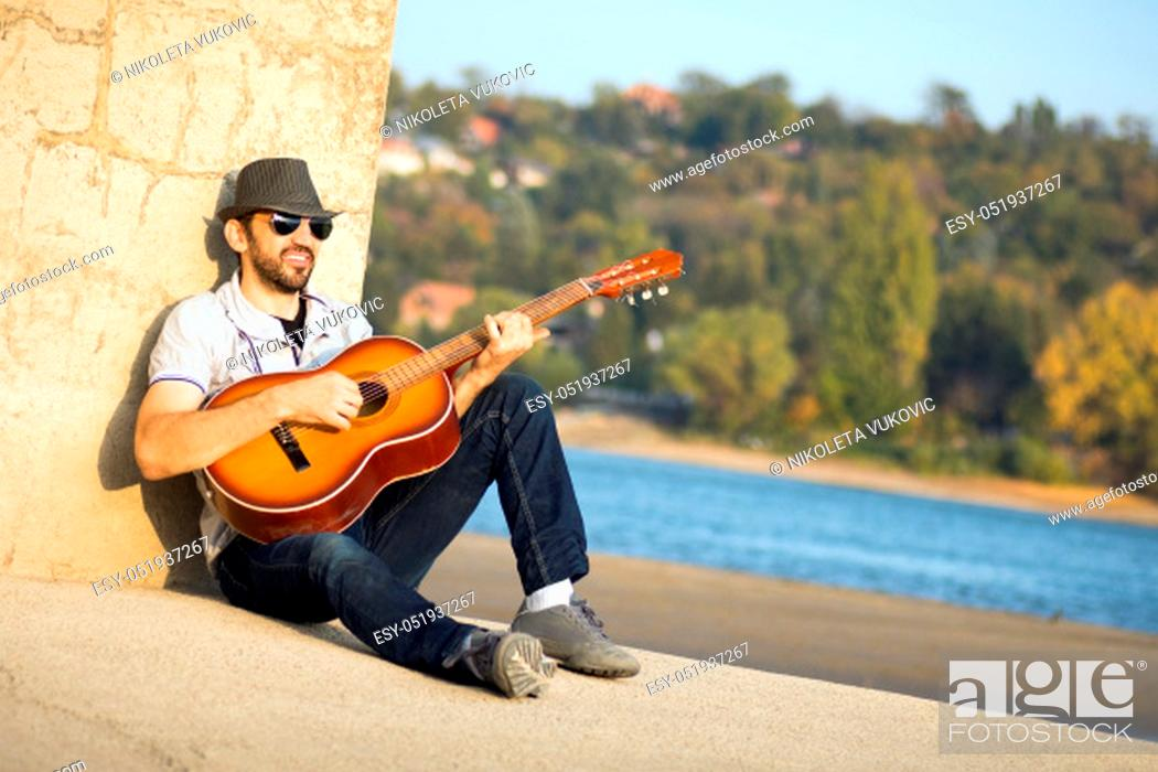 Imagen: The hipster guy is sitting and playing guitar outdoors on the beach at riverside.