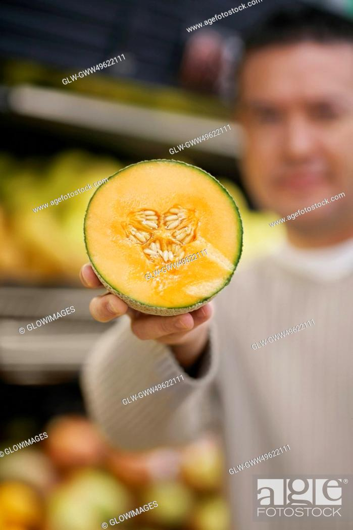 Stock Photo: Mid adult man showing the cross section of a cantaloupe.