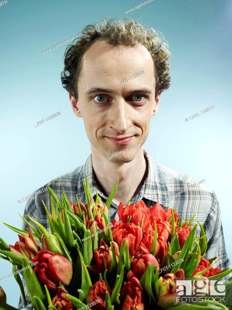 Stock Photo: A man holding a bouquet of tulips hopefully.
