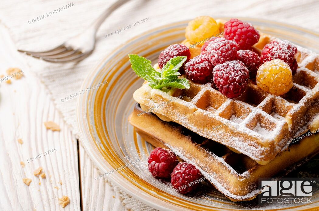 Stock Photo: Belgian waffles served with raspberries and mint leaf dusted with powdered sugar on white wooden kitchen table.