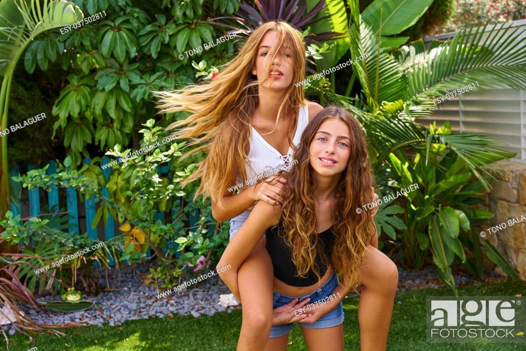 Stock Photo: Best friends teen girls piggyback on backyard garden happy smiling.