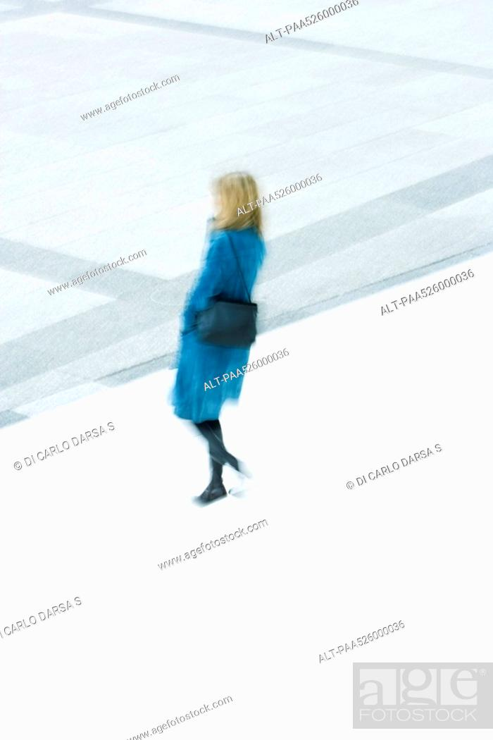 Stock Photo: Woman in blue overcoat descending stairs.