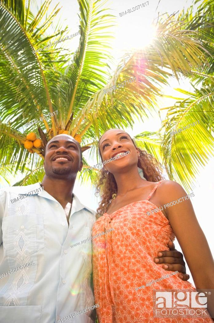 Stock Photo: African American couple hugging under palm tree.