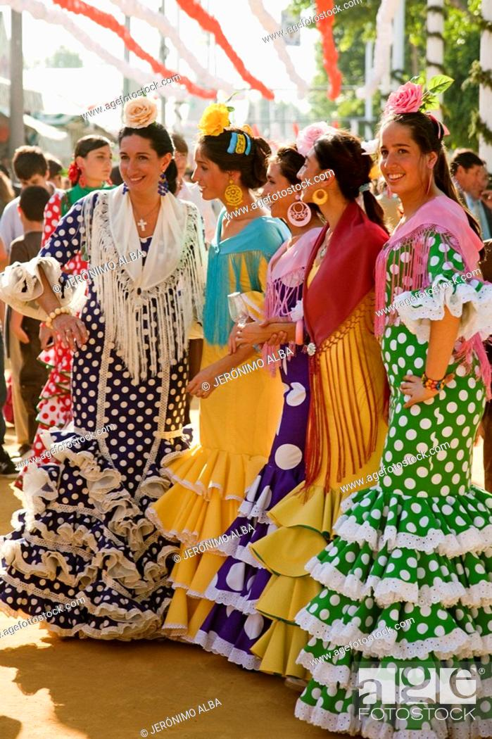 Imagen: Women wearing a flamenco style dress in the Seville Spring Fair, Seville, Andalusia, Spain.