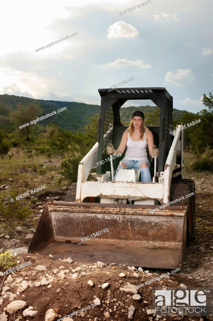 Stock Photo: Female construction worker operating wheel loader.
