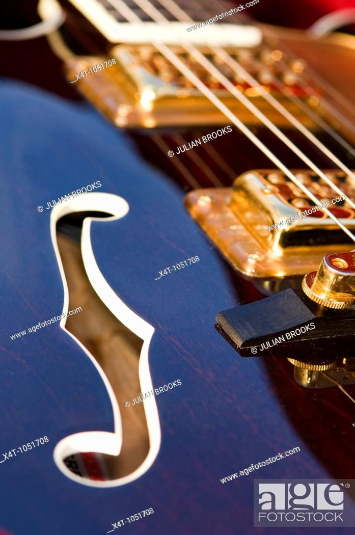 Stock Photo: The violin hole and pickups/strings on an electric guitar Gretsch - detail.