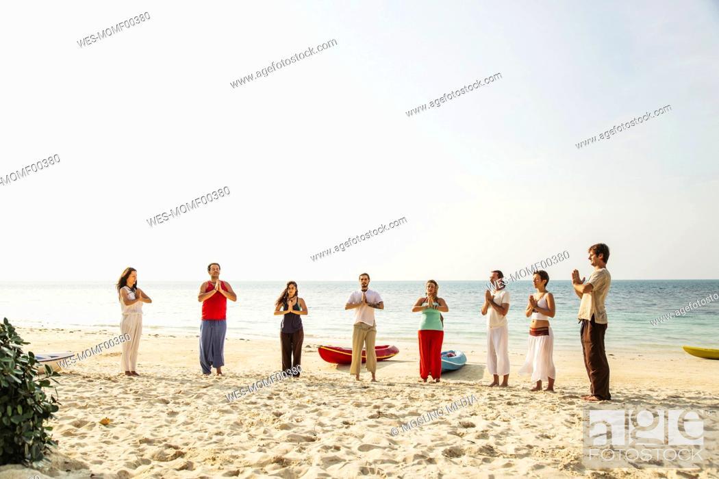 Stock Photo: Thailand, Koh Phangan, group of people doing yoga on a beach.