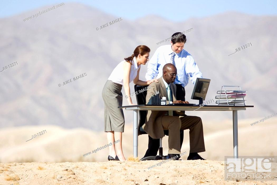 Stock Photo: Businessman and woman looking over colleagues shoulders at computer screen on desk in desert.