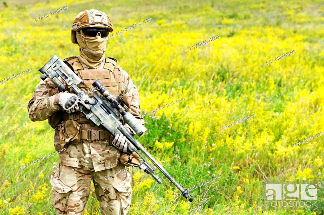 Imagen: Equipped and armed special forces soldier in the blooming field with copy space for text.