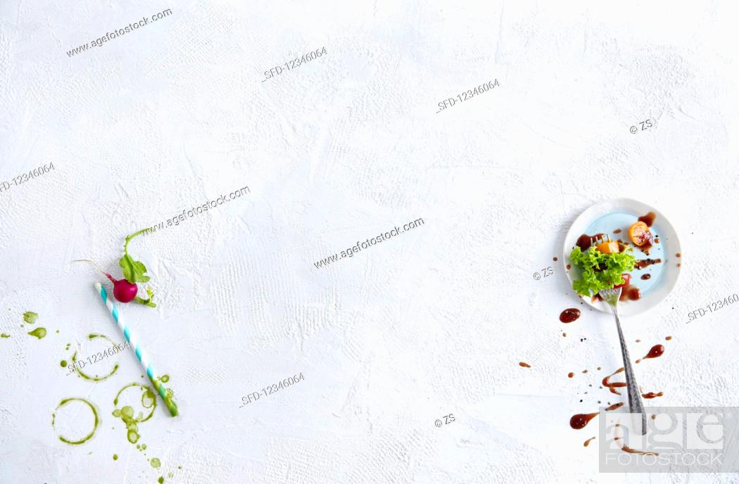 Stock Photo: Green smoothie stains, a straw, a radish, and lettuce leaves.