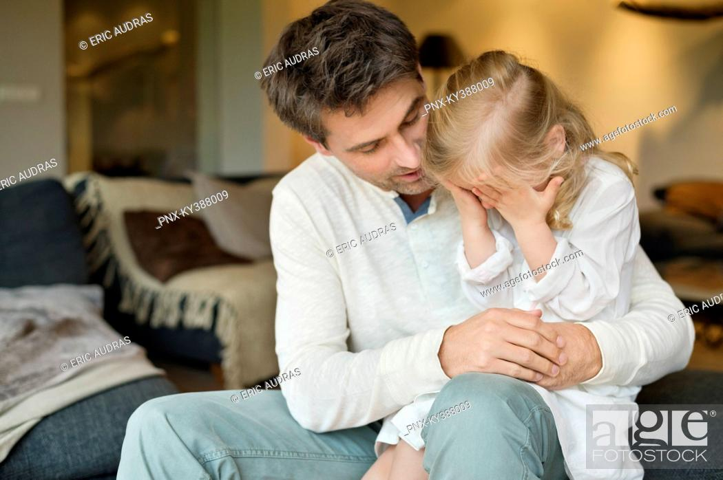 Stock Photo: Man holding his cute daughter covering her eyes with hands.