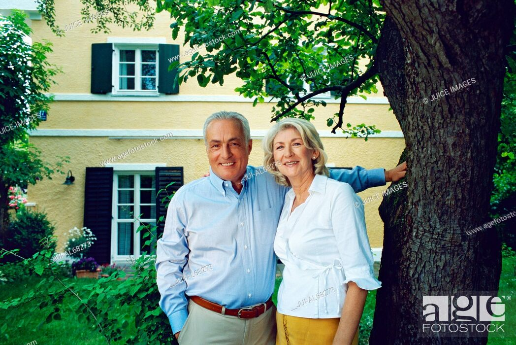 Stock Photo: Mature couple posing together in front of a yellow house.