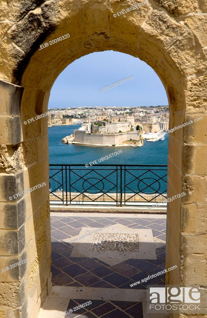 Stock Photo: Fort Saint Angelo on Vittoriosa one of the Three Cities in Valletta Harbour seen through an arch in the Upper Barrakka Gardens in Valletta.