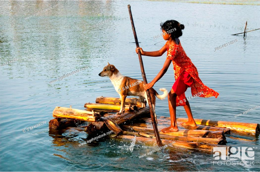 Stock Photo: A girl carries her pet by a banana raft aftermath of a devastating cyclone The cyclone Aila swept over the coastal areas of Bangladesh on May 25.
