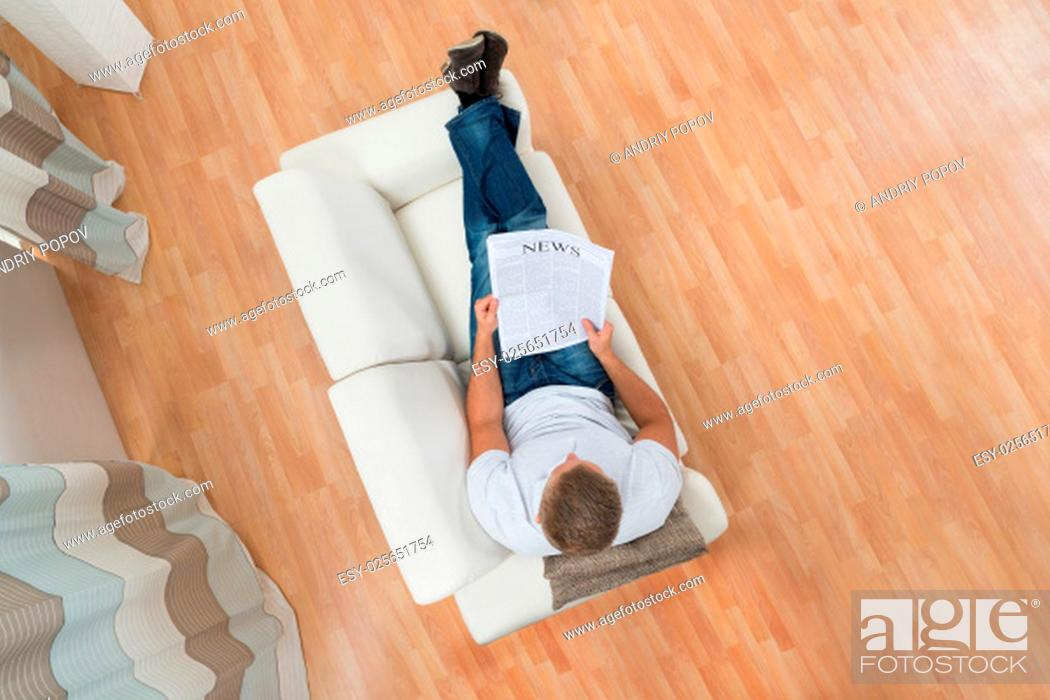 Stock Photo: Young Happy Man On White Sofa With Newspaper.