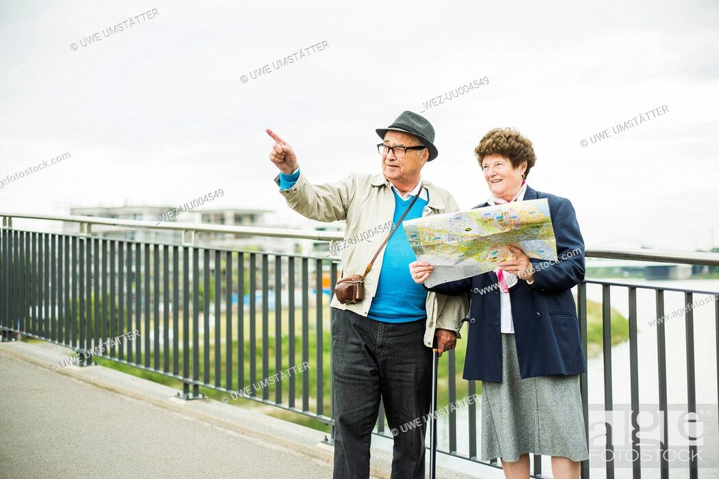 Stock Photo: Senior couple with map standing on a bridge.