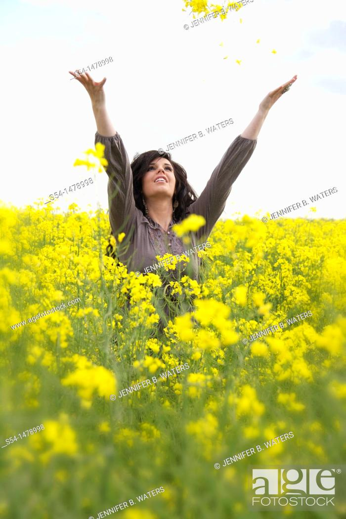 Stock Photo: A happy young caucasian woman in a field of canola.