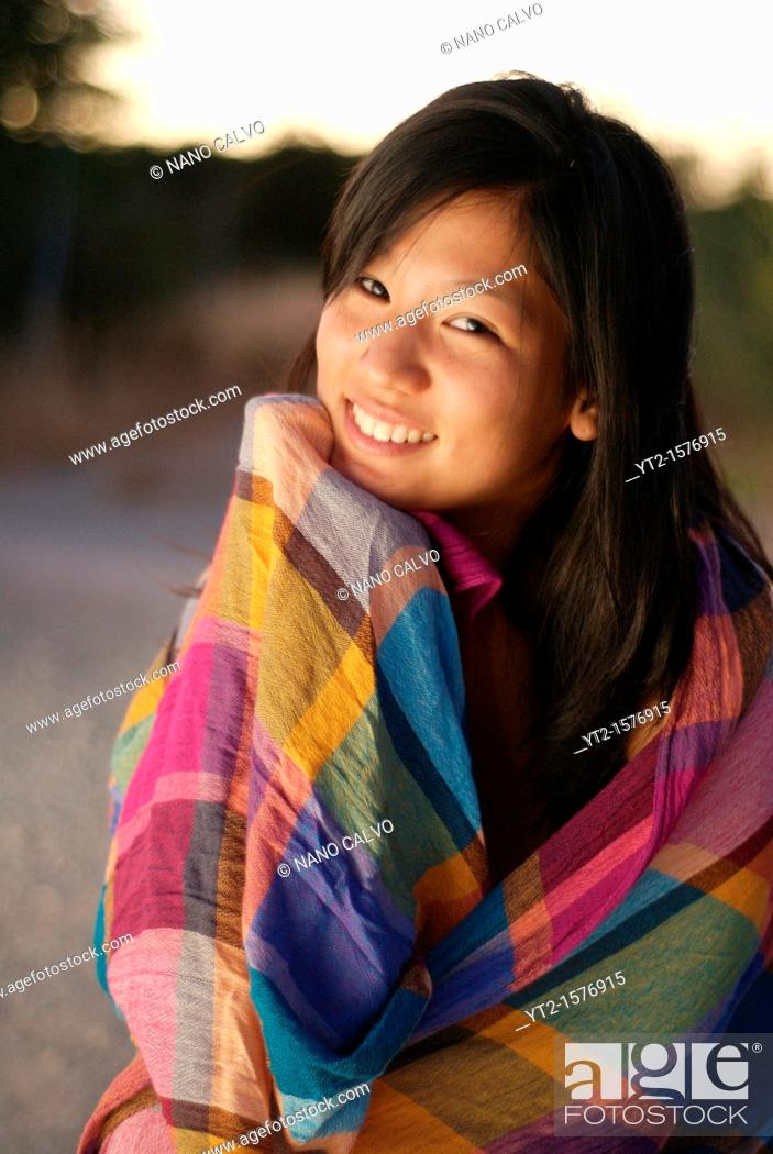Stock Photo: Cute young asian woman at sunset.