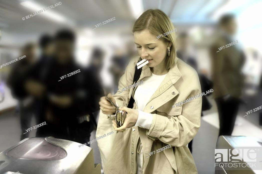 Stock Photo: fashionable woman searching for ticket in purse to enter public transport system, metro, in Paris, France.