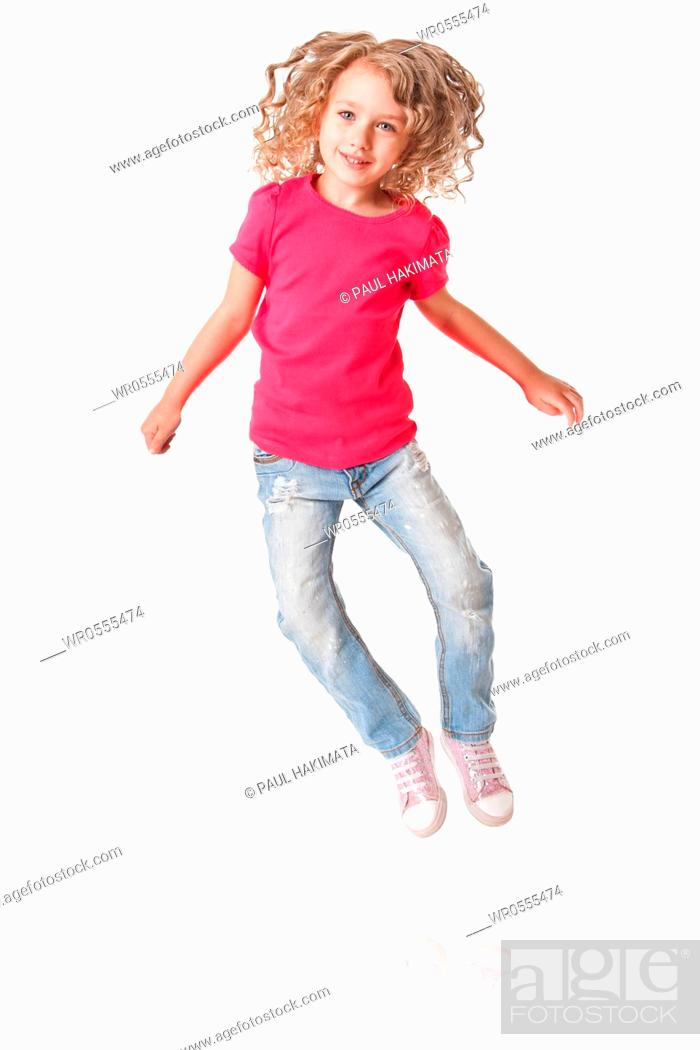 Imagen: Cute happy smiling jumping of joy girl with heels together in pink shirt and jeans, isolated.