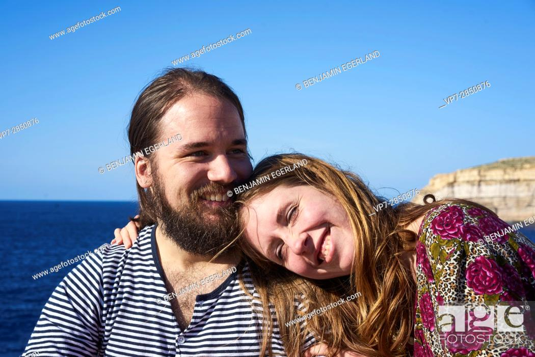 Imagen: happy girlfriend leaning on her boyfriend's shoulder and enjoying vacations, next to the sea in Gozo, Malta, Europe.