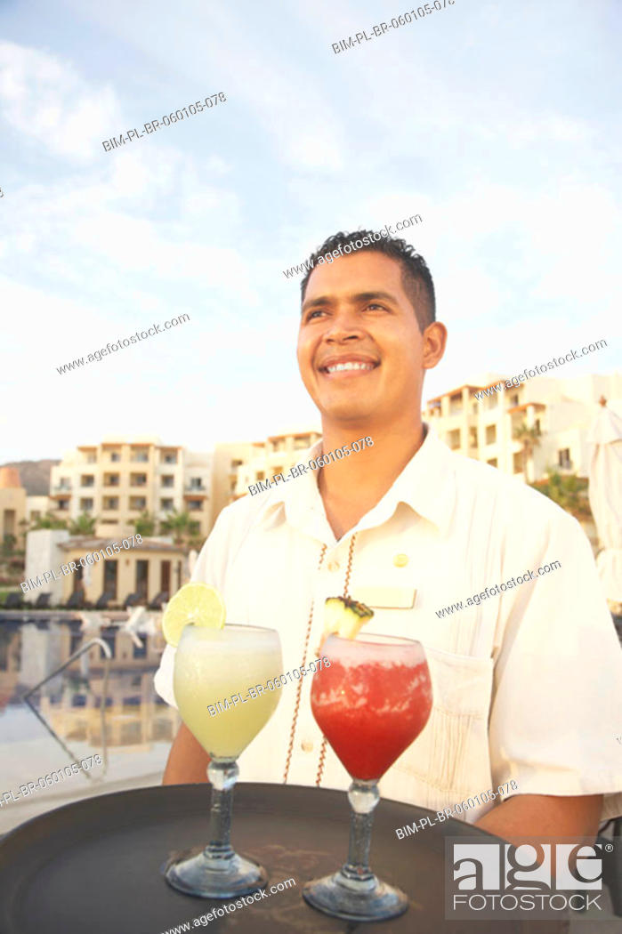 Stock Photo: Hispanic male waiter with a tray of drinks, Los Cabos, Mexico.