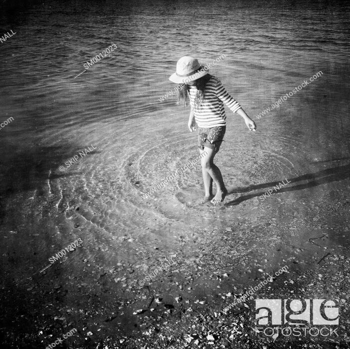 Stock Photo: Little girl wading through the water at the beach.