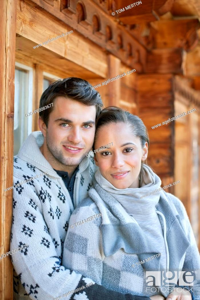 Stock Photo: Portrait of smiling couple hugging on cabin porch.