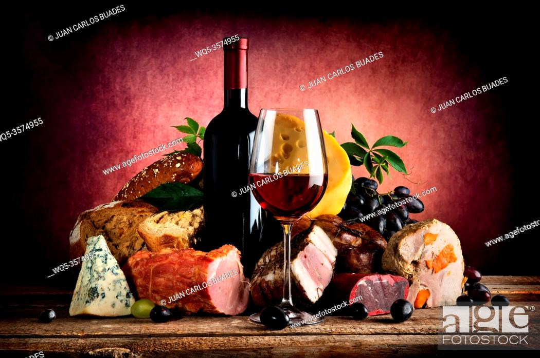 Stock Photo: Red wine and different food on a wooden table.