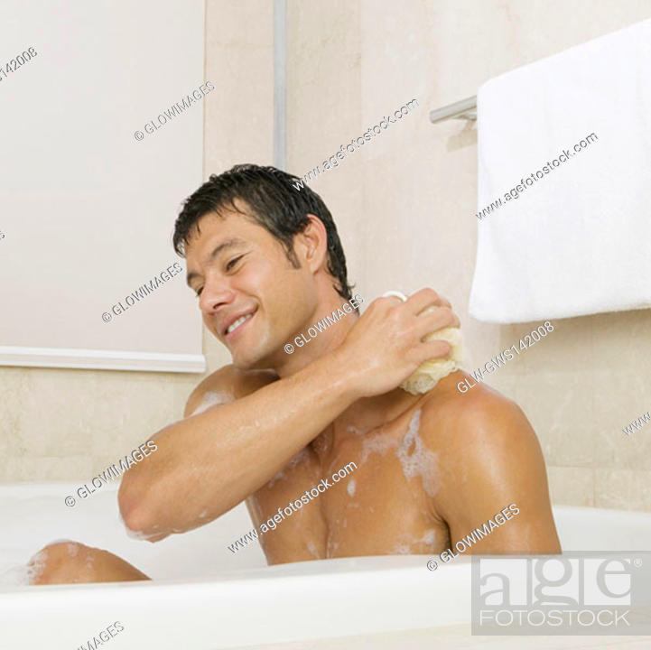 Stock Photo: Mid adult man scrubbing his body in the bathtub.