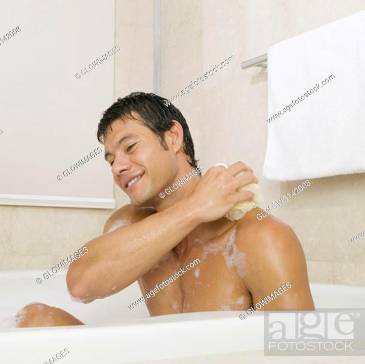 Stock Photo: Mid adult man scrubbing his body in the bathtub.