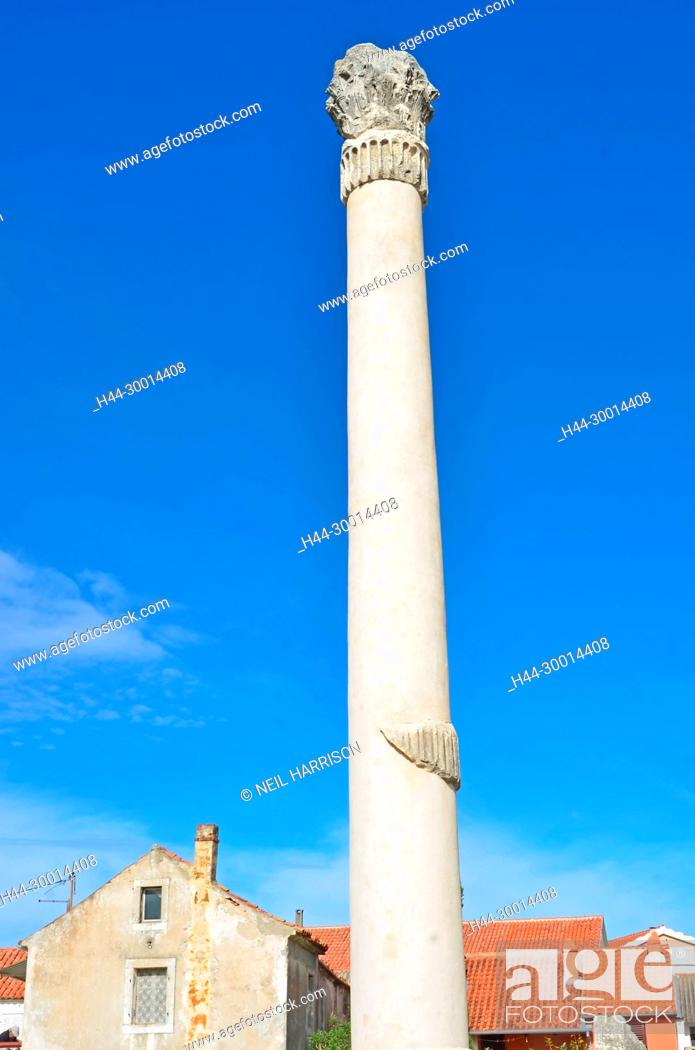 Stock Photo: A reconstructed tall roman column with a corinthian capital from a ruined temple in the middle of a town.