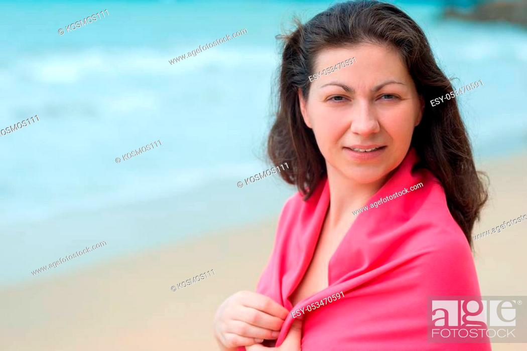 Stock Photo: portrait of a brunette woman wrapped in a towel at the beach.