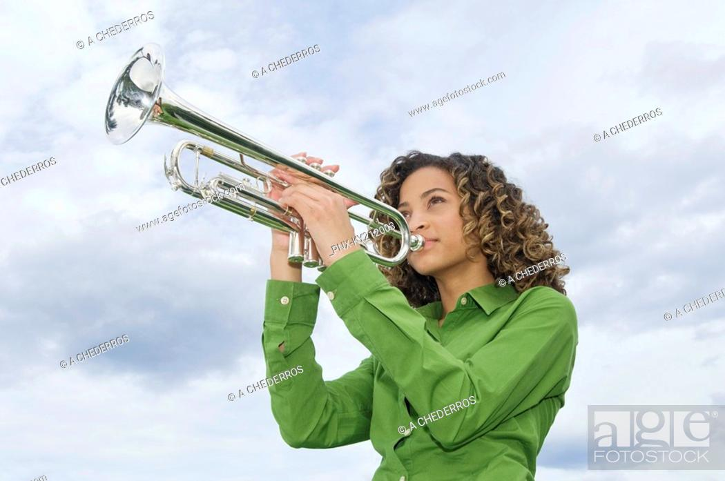 Stock Photo: Low angle view of a girl playing a trumpet.